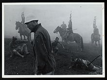 Kurosawa, a tall, thin man in early middle age facing left, wearing modern clothes topped by a soft white cap, strolls through a foggy landscape, as behind him various actors in medieval Japanese garb appear on horseback or lying or sitting on the ground.