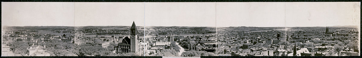 A panorama from 1909, in sepia, shows a view of the city perpendicular to the river; there are numerous church steeples and the city hall tower can be seen left of center.