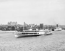 A white steam ship is seen near the shore of the Hudson River in front of the downtown area of Albany; the New York State Capitol can be seen in the background.