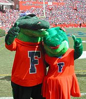 Two alligator mascots with their arms wrapped around each other posing for a photo.