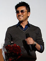 Chinese man with sunglasses smiling holding microphone in one hand and bouquet of roses in the other