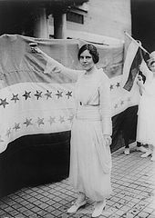 Alice Paul stands before the Woman Suffrage Amendment's ratification banner.