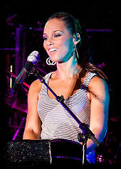 An African-American female singing into a microphone on a stand. She is wearing large hoop earrings and a silver sleeveless shirt.