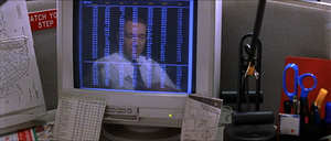 A computer monitor on a busy cubicle desk. The monitor displays a spreadsheet in seven columns which span the height of the screen. The monitor also shows the reflection of a middle-aged man in a shirt and tie, sitting close to the desk and wearing a telephone headset. The contrasts—the monitor's dark background, and the lightness of the text and the man's shirt—make the reflection more prominent between and behind the numbers.