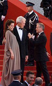 Angelina Jolie et Clint Eastwood, face au public, sur le tapis rouge, montant les marches du palais du Festival de Cannes, Gilles Jacob leur parlant