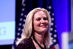 Photograph of Ann Romney taken in a hall, with large video screen and American flag in background