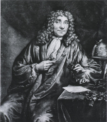A man wearing a long, curly wig and a full robe is sitting, looking out. His left arm rests on a small table, with his left hand holding a box. Behind him is a globe