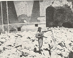A sepia photograph shows a soldier, gun in hand, standing amidst the rubble of the destroyed synagogue. Behind him, remnants of the eastern wall shows a painted fresco of Mount Sinai and two arched tablets symbolising the ten commandments.