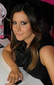 Head and shoulders of Tisdale in her twenties. Her dark brown, straight hair is parted in her left, and falls over her right ear.