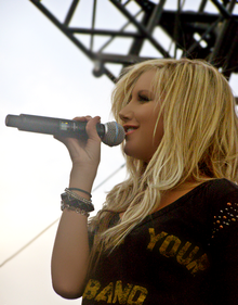"""A young blond female singer on a stage sings into a microphone, holding it with her right hand. She is using a black blouse with the words """"Your"""" and """"Band"""" printed on it in a yellow color and few bracelets on her right hand."""