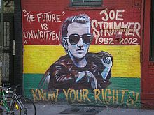 """A photograph of the painting of the memorial mural of Joe Strummer on the wall of the Niagara Bar in the East Village in New York City. The mural depicts Joe (center) surrounded by the words """"THE FUTURE IS UNWRITTEN"""" (on the left), """"JOE STRUMMER 1952–2002"""" (on the right), and """"KNOW YOUR RIGHTS!"""" (bottom) on a horizontal tricolour of red, yellow, and green background"""