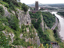 Rocky side to a gorge with a platform in front of a cave half way up. To the right are a road and river. In the distance are a suspension bridge and buildings.