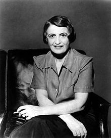 Half-length monochrome portrait photo of Ayn Rand, seated, holding a cigarette