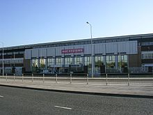 A three-storey building composed of glass windows and grey concrete stands across from a tarmac road and in front of a clear blue sky. A road passing horizontally in the foreground is divided by a pavement and metal barriers. The building's entrance appears central and is flanked by mirrored-glass windows and is marked by a red sign with the text BAE SYSTEMS.