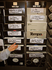 Two vertical columns of binds holding records in paper sleeves for sale. Lettering identifying each bin is by hand.