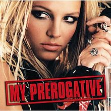 """The face of a blonde woman. She is holding a microphone in her hand next to her head, while looking towards the left side of the picture. She is wearing different rings in her fingers. She is wearing a black vest. On the lower part of the image, the words """"My Prerogative"""" are written in red capital letters inside a box of the same color."""
