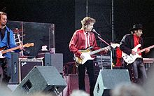 Dylan and members of his band perform onstage. Dylan, wearing a red shirt and black pants, plays an electric guitar and sings.