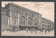 Carte postale montrant partiellement et en perspective la gare de Strasbourg, un imposant bâtiment de style wilhelmien, avec son entrée par la partie centrale et son aile droite. Ses façades, librement inspirées du style Renaissance, s'ouvrent par de grandes baies vitrées. Devant l'auvent de la gare stationnemnt plusieurs personnes et chevaux attelés ou montés. Les impressions en allemand Strassburg et Zentralbahnhoff figurent au-dessus de la gare parmi d'autres mots manuscrits.