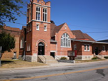 Old red-brick church building with arched entrance and stained-glass window