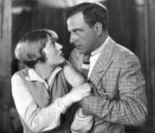 A middle-aged man wearing a plaid jacket and boldly striped tie grabs a younger woman wearing a sweater vest by the arm. Her hand tugs at his as they gaze into each other's eyes, he fiercely, she with surprise or concern.