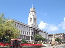 Barnsley Town Hall on a fine day.  The Town Hall itself is visible behind some gardens; the building is made of white stone and has an impressive clock tower