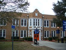 an old two story brick building with a orange doors and blue banners