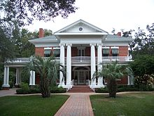 an old southern neoclassical-styled mansion with manicured lawn and palm trees