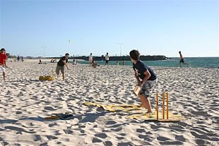 children playing cricket on the beach