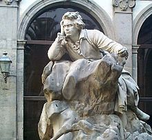 Statue of a man sitting on a rock, with an intent look.