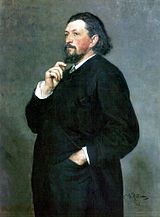A middle-aged man with medium-length dark hair and a beard, wearing a dark suit, with one hand in his trouser pocket and the other hand on his chin