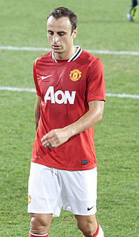 A tall, dark-haired man wearing a red shirt and white shorts stands in a formative pose.