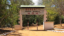 A dirt road runs under a decorated, arching sign demarcating the Berenty Private Reserve.