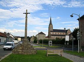 La croix de pierre sur son socle en escalier et l'église