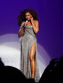 Photo montrant une femme qui chante sur scène, vêtue d'une robe d'argent avec des sangles tombant sur un bras et longs, cheveux bouclés et sauvages.
