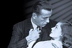 Black-and-white image of a man and a woman, seen from mid-chest up, their faces in profile, gazing into each others' eyes. He embraces her in a dip with his right arm and holds her right hand to his chest with his left hand. He wears a pin-striped suit and a dark tie. She wears a white top. On the left, the background is black; on the right, it is lighter, with a series of diagonal shadows descending from the upper corner.