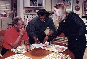 Three people on a TV set.