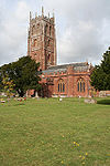 Red stone building with square tower. In the foreground is a graveyard.