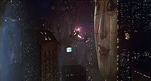 A screenshot of a police spinner flying through a cityscape next to a large building which has a huge face projected onto it. In the distance a screen can be seen with writing and pictures on it