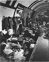 View along a tube station platform; people are sitting and lying on low beds in the track area next to the platform, others sit on the edge of the platform. A row of coats hangs from hooks on the tunnel wall. A couple with a baby are sitting in the foreground looking at the camera