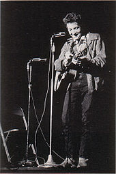 Dylan with his guitar onstage, laughing and looking downwards.