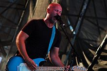 Bob Mould—a middle-aged Caucasian man with a shaved head and short facial hair wearing a black t-shirt—plays a blue guitar and sings into a microphone