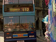 A drag queen (Wynnie La Freak) stands in front of a bus causing it to stop.