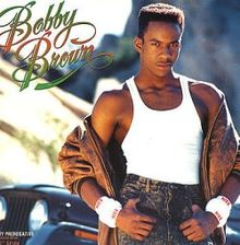 """An African American man. He looks towards the camera with a commanding face. He wears a white wifebeater, jeans and a brown leather jacket. The background is a blurred street, with a truck behind him. On the upper left corner of the image, the words """"Bobby Brown"""" are written in flourished red and green letters. On the upper left corner, the word """"My Prerogative"""" is written in very small white capital letters."""