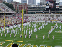 A football stadium with a marching band in white uniforms on the field, with the goal post in the foreground and various buildings in the background