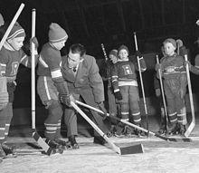 Photo noir et blanc de jeunes joueurs écoutant les conseils de leur entraîneur.