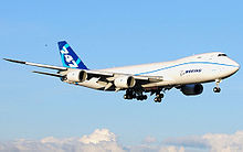 Quarter view of quadjet on approach over clouds.