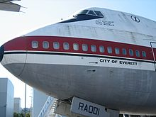 A side view of the nose of 747 prototype, which is painted white, with a red wide cheatline, and a metallic underside
