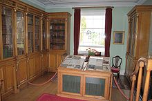 Photograph of a laboratory, with glass-encased, wooden bookcases on two walls and a window on the third. There is a display case in the middle of the room.