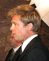 A side view of a Caucasian male, who is facing to the left, with light brown hair. He is wearing a black suit and tie with a white shirt. Another Caucasian male, also wearing a suit, is visible in the background.