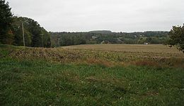Photo from the top of a hill looking at rising ground in the distance